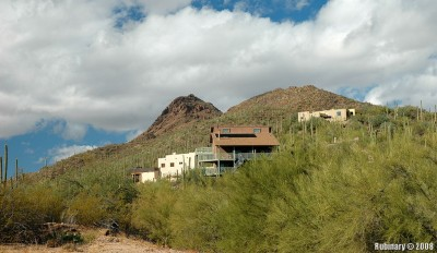 House on the hill of the mountain covered in Saguaros. Outskirts of Tucson.