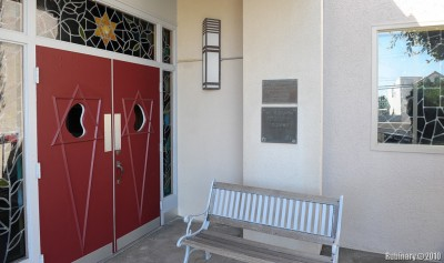 Synagogue entrance with the plaque on the wall.