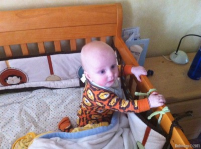 He got onto his knees and is holding onto the crib's rail