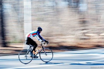 Cyclist. Taken at f/16. The blur on the cyclist is my hands shaking. Has nothing to do with the lens.