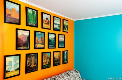 National Park posters on orange wall.