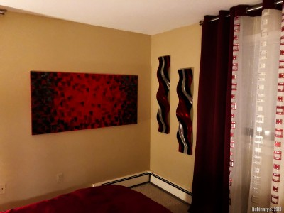And another wall of our bedroom. Some modern abstract art in red and black. The metals plates are custom hand made pieces of art.